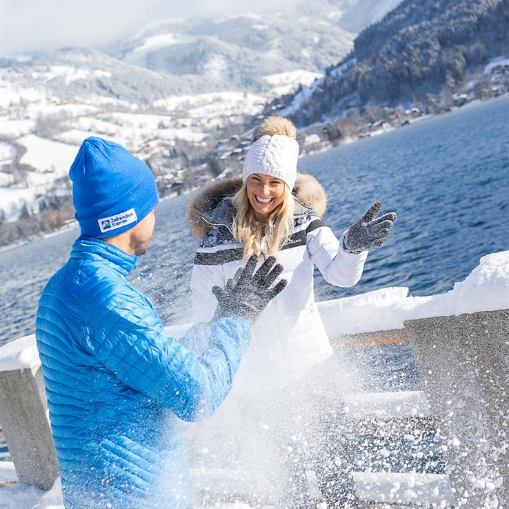 Couple at snowball fight on the lake shore of Lake Zell