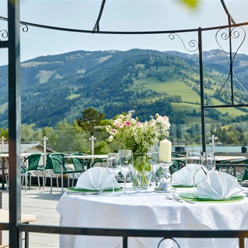 Festively laid table for two on the roof terrace of the Romantik Hotel with a view of Lake Zell