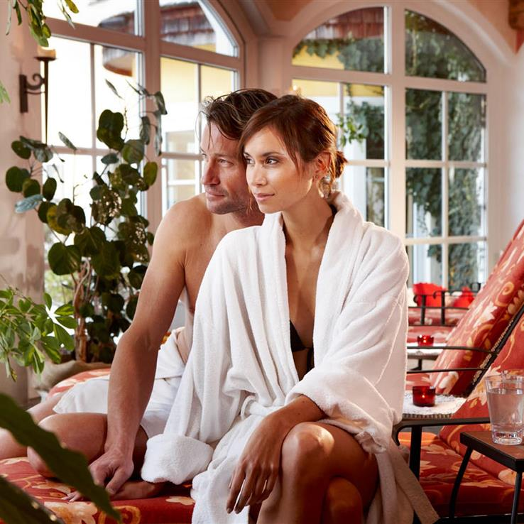 Couple with bathrobe and drinks in the wellness area