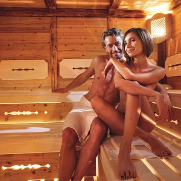 Couple sitting on towel in sauna