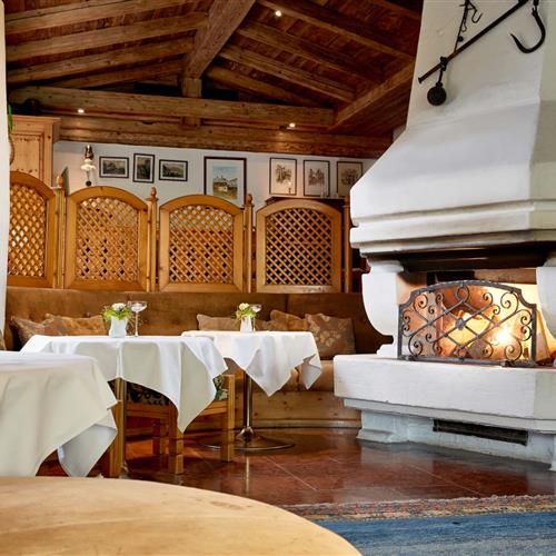 Open, brick fireplace with fire and cozy seating in the Romantikhotel Zell am See