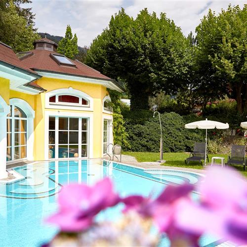 Outdoor pool in the garden of the Romantikhotels with violet flowers