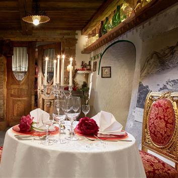 Festively laid table for two in the wine cellar with candlelight