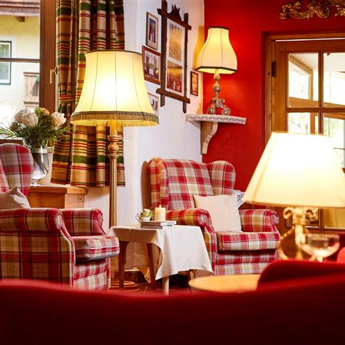 Armchairs with lamp in the lounge with open fireplace in the 4* Romantikhotel Zell am See