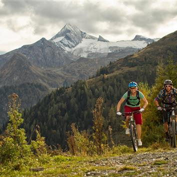 Two mountain bikers on gravel road with mountain panorama