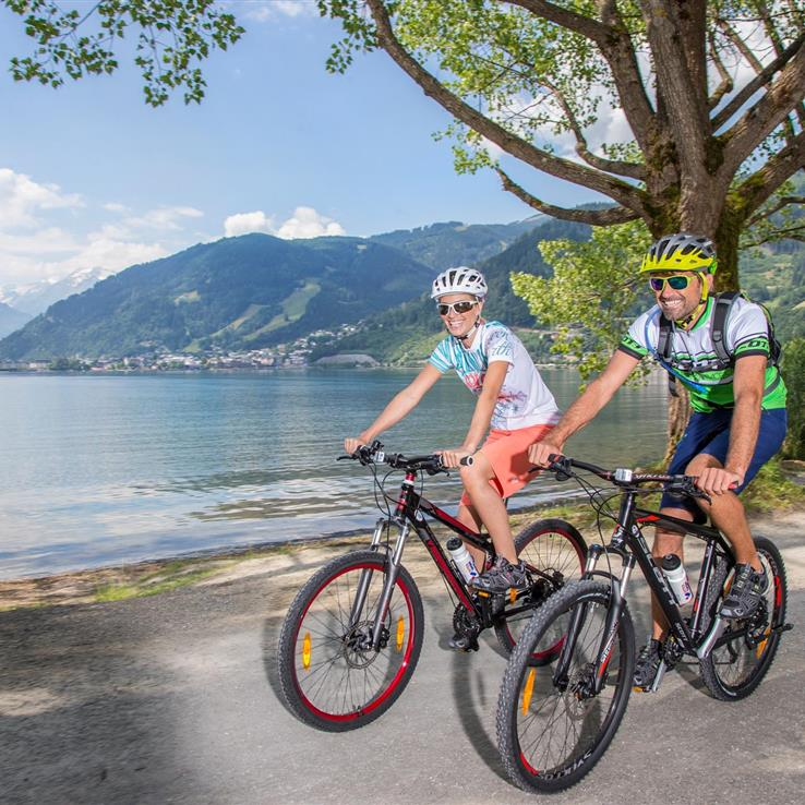 Couple with mountain bikes on the banks of Lake Zell, Salzburg