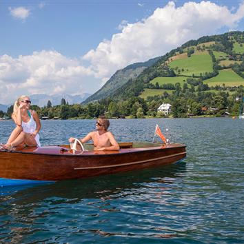 Couple in electric boat at lake Zell, Salzburg