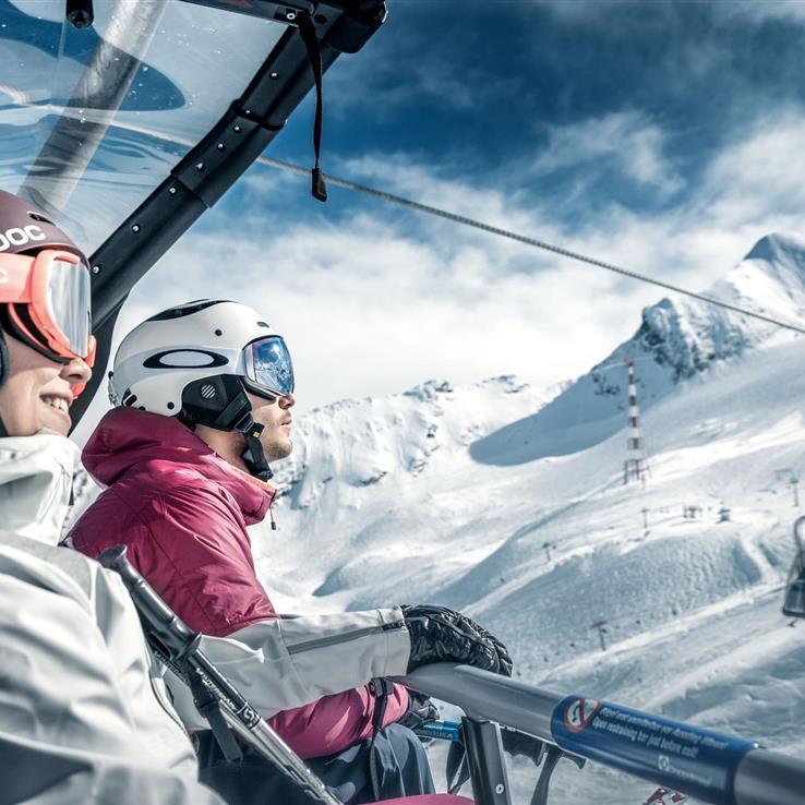 Couple in modern chairlift - glacier jet in Kaprun