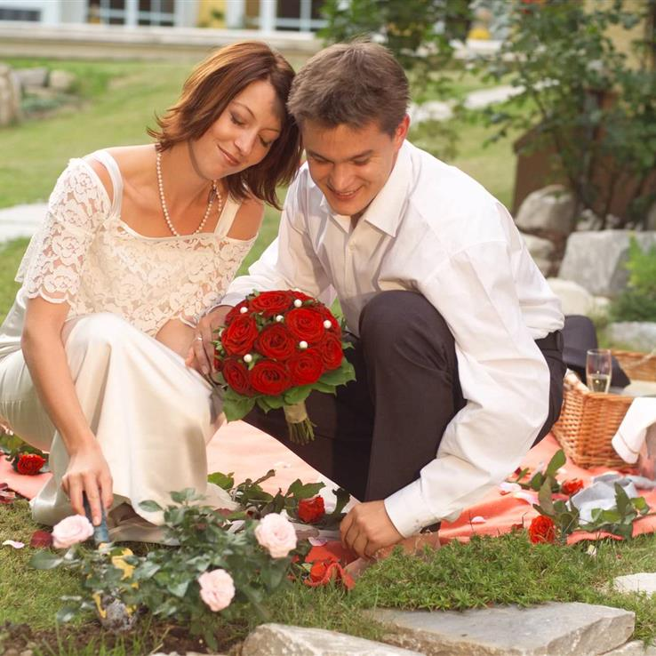 Wedding couple in the garden with picnic basket