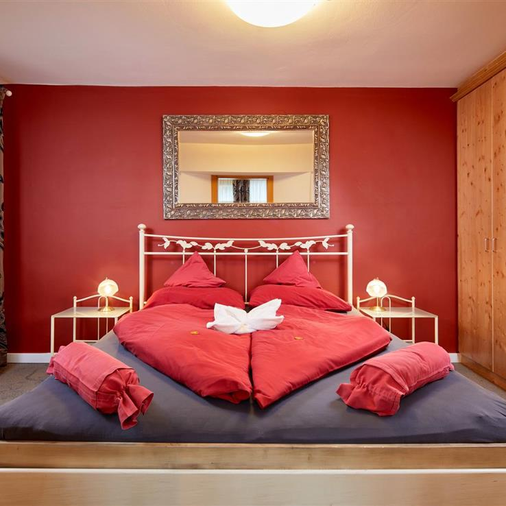 Double bed with red, heart-shaped bed linen