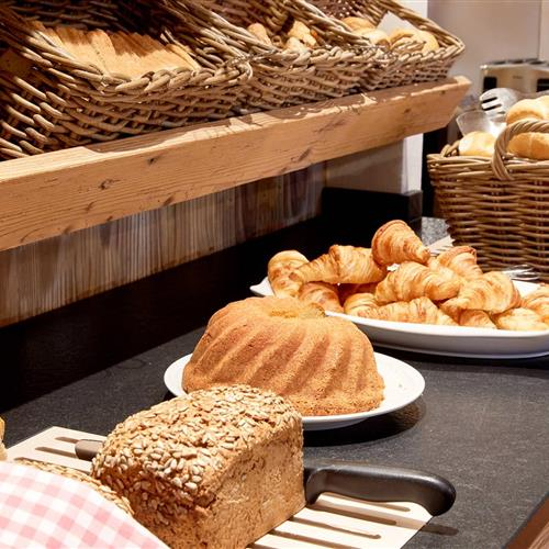 Croissantes, cake and bread standing on a sideboard