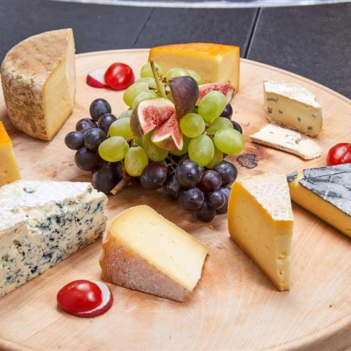 Wooden board with different types of cheese, garnished with grapes and figs
