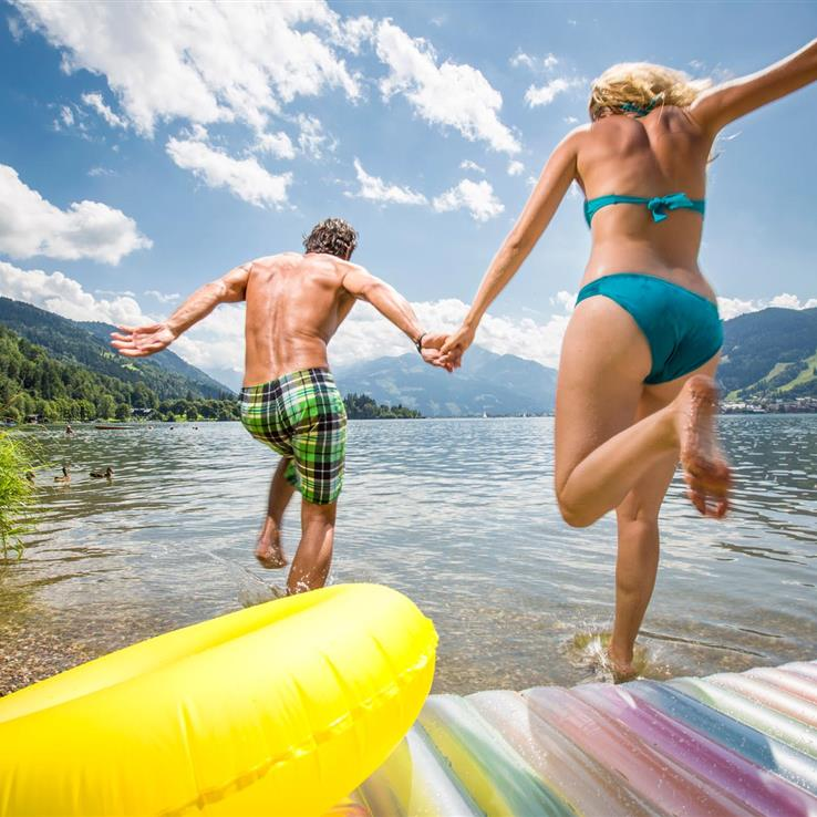 Couple jumping into Lake Zell