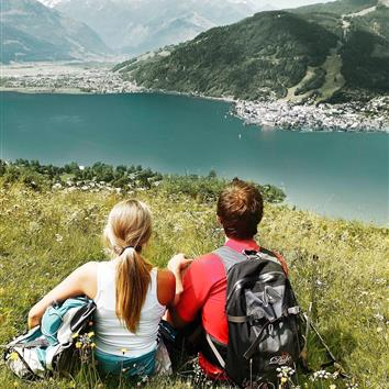 Couple sitting with hiking pack with panoramic view on the lake Zell