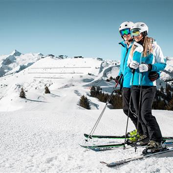 Couple standing with ski standing with panoramic view on the slopes